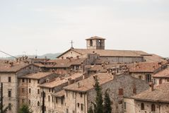 Glimpse with some typical houses roofs and fireplaces. Part of medieval city with storical stones constructions and little church from the top of Gubbio Stock Photos