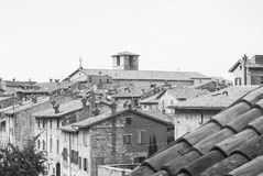 Glimpse with some of typical houses roofs and fireplaces. Part of medieval city with storical stones constructions and little church from the top of Gubbio Stock Photo