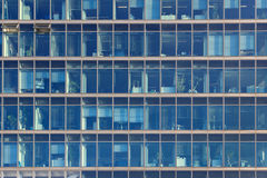 Glimpse into the workplaces of an office building with blue glas. Glimpse into the workplaces of an office building with large blue tinted glass windows Stock Image