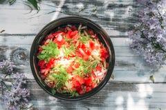 Gliniana filiżanka z jarzynową sałatką od pomidoru, ogórków i basila na fonederevyanny stary stół dekorował gałąź zdjęcia royalty free