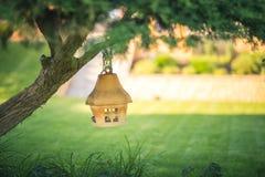 Gliniany lub ceramiczny ptasi dozownika obwieszenie na drzewie w ogródzie, miękki rozmyty tło zdjęcie royalty free