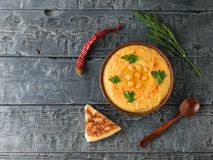Gliniany puchar z świeżym hummus i chili pieprzem na ciemnym drewnianym stole najlepszy widok najlepszy widok Obraz Stock