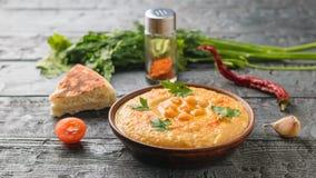 Gliniany puchar z świeżym hummus, kawałek pita pomidory na ciemnym drewnianym stole, chlebowi i pokrojeni Zdjęcie Stock