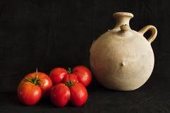 Gliniany słój i trzy czerwonych pomidoru odizolowywających na czerń Obraz Stock