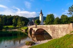 Église du SV Jean-Baptist et un pont par le lac Bohinj Photographie stock libre de droits