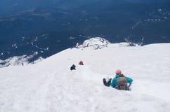 glissading在山山顶下的登山人 免版税库存图片