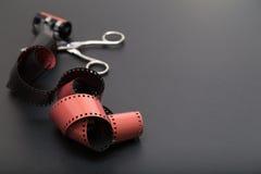 Glisse des diapositives de petit pain de film avec des ciseaux Photo stock