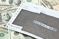 Glissement de feuille de paie sur la pile des billets de banque de dollar US Image libre de droits