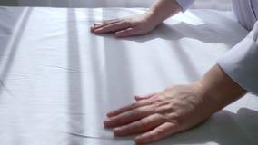 Glissement des mains femelles du masseur sur le tissu blanc, feuille stérile sur le plan rapproché de table de massage clips vidéos