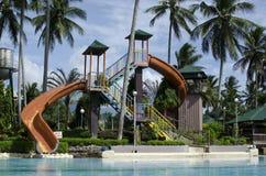 Glissière d'eau de piscine dans une station de vacances plantée avec des arbres de noix de coco image libre de droits