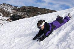 Glissière de petite fille sur la neige pendant des vacances d'hiver image stock