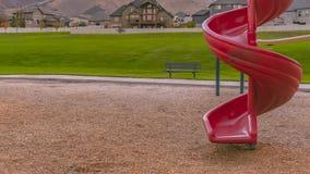 Glissière en spirale rouge avec des maisons de montagne et la vue de pelouse photo stock