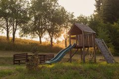 Glissière extérieure en bois de terrain de jeu en parc rural de jardin, coucher du soleil d'enfants images stock