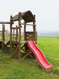 Glissière rouge de construction en bois de rampement sur le terrain de jeu moderne d'enfants Photo libre de droits