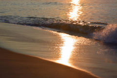 Glistening and Golden Waves at Sunrise Stock Photography
