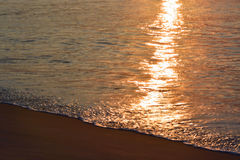 Glistening and Golden Waves at Sunrise Stock Images