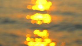 Glistening and shimmering golden ocean, sea surface at sunset over tropical beach, sunrise or twilight. Sun reflections. Off lake water background. De-focused stock video footage