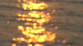 Glistening and shimmering golden ocean, sea surface at sunset over tropical beach, sunrise or twilight. Sun reflections. Off lake water background. De-focused stock footage