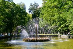 A glistening spraying fountain. A fountain is spraying with glistening water under the sunshine in a park in Russia. The fountain pool is surrounded by tall royalty free stock photography