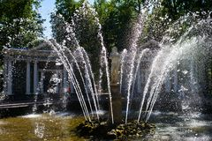 A glistening spraying fountain. A fountain is spraying with glistening water under the sunshine in a park in Russia stock images