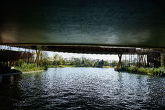 Glistening water surface under bridge Royalty Free Stock Photography