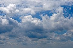 GLISTENING WHITE CLOUDS SET AGAINST BLUE SKY Stock Photo