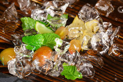 Glistering cold ice cubes. Ice with yellow berries, lime segments, carambola and mint twigs. Ingredients for summer cocktails. Royalty Free Stock Image