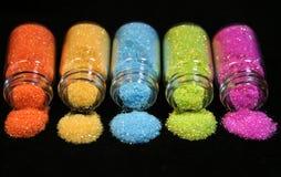 Glitter. Jars of blue, green, orange, yellow and pink glitter Royalty Free Stock Photo