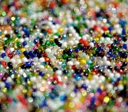 Glitter beads. Multi-colored, glass beads lying on the plane. The light is reflected on it with colored highlights Royalty Free Stock Photo