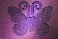 Glitter butterfly. Purple sparkly glitter butterfly on a pink sparkly glitter background royalty free stock photography