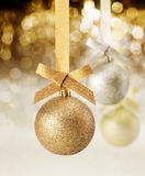 Glitter Christmas ornament and party lights. Hanging golden glitter textured Christmas ornament against a background of twinkling party lights royalty free stock images