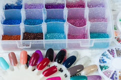 Glitter. Different colors glitter nail decorations in a box and samples for nail polish stock photo