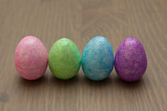 Glitter Easter Eggs. Four glittery pastel Easter eggs on a wood grained surface Stock Image