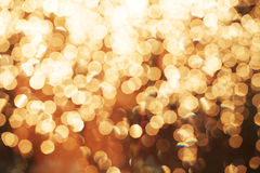 Glitter festive christmas lights background. light and gold defocused texture