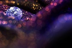Glitter and glow soft multi colored  bokeh shining with big natural jewelry precious stone. Royalty Free Stock Photo