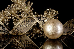 Glitter Gold Christmas Ornament. A round glitter gold Christmas ornament with gold and black ribbon on black reflective surface with gold bokeh background Stock Image