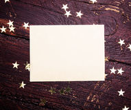 Glitter golden stars  with blank paper on grunge wood Royalty Free Stock Image