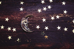 Glitter golden stars and glass moon on grunge wood Royalty Free Stock Photography