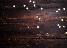 Glitter golden stars on grunge wood background. Royalty Free Stock Images