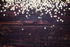 Glitter golden stars on grunge wood background. Royalty Free Stock Photos
