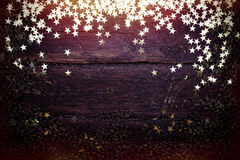 Glitter golden stars on grunge wood background. royalty free stock image