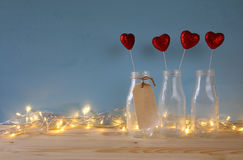 Glitter hearts in the glass vases on wooden table. Valentines day background. Glitter hearts in the glass vases on wooden table stock image