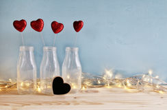 Glitter hearts in the glass vases on wooden table. Valentines day background. Glitter hearts in the glass vases on wooden table stock images