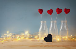 Glitter hearts in the glass vases on wooden table Stock Photo