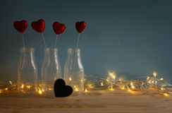 Glitter hearts in the glass vases on wooden table. Valentines day background. Glitter hearts in the glass vases on wooden table royalty free stock photos