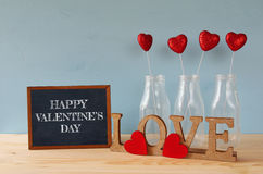 Glitter hearts in the glass vases on wooden table Stock Images