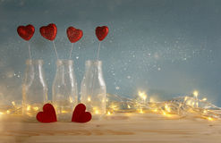 Glitter hearts in the glass vases on wooden table. Valentines day background. Glitter hearts in the glass vases on wooden table royalty free stock image