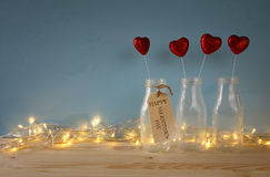 Glitter hearts in the glass vases on wooden table. Valentines day background. Glitter hearts in the glass vases on wooden table stock photography