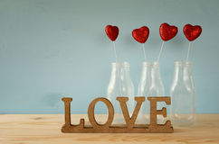 Glitter hearts in the glass vases on wooden table. Valentines day background. Glitter hearts in the glass vases on wooden table royalty free stock photography