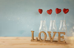 Glitter hearts in the glass vases on wooden table. Valentines day background. Glitter hearts in the glass vases on wooden table stock photo